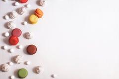Fond blanc avec la meringue, les macarons et les canneberges en sucre Photographie stock