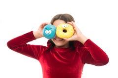 Fond blanc de beignet vitré de prise de fille Fille d'enfant affamée pour le beignet doux Niveaux de sucre et nutrition saine Bei images stock