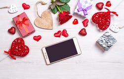 Fond blanc en bois avec des coeurs, des cadeaux, la rose de rouge et le smartphone Photos stock