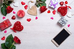 Fond blanc en bois avec des coeurs, des cadeaux, des roses rouges et le smartphone Images libres de droits