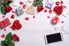 Fond blanc en bois avec des coeurs, des cadeaux, des roses rouges, le smartphone et des écouteurs Images stock
