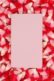 Fond blanc, rose et rouge de bonbons au maïs avec la carte rose vierge Image libre de droits