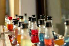Fond Bouteilles dans une boîte en bois remplie de boissons colorées photos stock