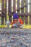 Fond brouillé, enfant à la barrière, avec un chien de jouet Photo libre de droits