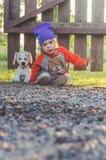 Fond brouillé, enfant à la barrière, avec un chien de jouet Photographie stock libre de droits
