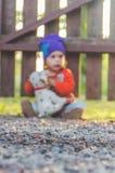 Fond brouillé, enfant à la barrière, avec un chien de jouet Photos stock