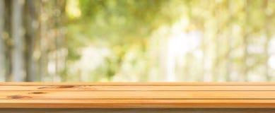 Fond brouillé par table vide de conseil en bois Table en bois brune de perspective au-dessus de fond de forêt d'arbres de tache f Photographie stock libre de droits