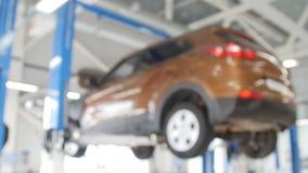 Fond brouillé : Technicien de voiture réparant la voiture dans le garage banque de vidéos