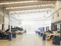 Fond brouillé : Technicien de voiture réparant la voiture dans le garage Images libres de droits