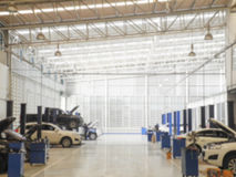 Fond brouillé : Technicien de voiture réparant la voiture dans le garage Photos stock