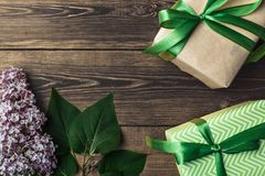 Fond brun en bois avec des feuilles de vert et un cadeau avec un gree Images libres de droits