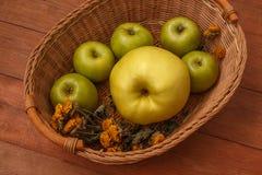 Fond brun en bois avec un panier des pommes vertes Photos stock