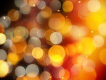 Fond chaud rougeoyant d'or avec des points culminants éclatants et des lumières rondes brouillées jaunes et argentées molles images libres de droits