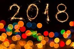 Fond circulaire abstrait de bokeh de lumière de Noël et écrit 2018 avec des feux d'artifice d'étincelle Photo stock