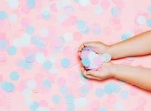 Fond coloré de confettis avec des mains du ` s d'enfant image libre de droits