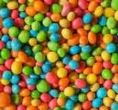 Fond coloré de petites formes rondes de sucrerie lumineuse Bonbons abstraits avec des raisins secs ou le bourrage nuts Photos stock