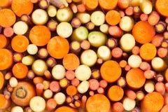 Fond coloré des carottes coupées en tranches assorties Photo stock