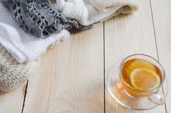 Fond confortable et mou d'hiver La tasse de thé et chauffent les vêtements tricotés Image stock