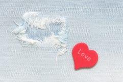 Fond déchiré de denim avec un coeur rouge et l'amour de mot Photos libres de droits