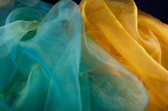 Fond décoratif fait de tissu soyeux transparent vert et jaune Photographie stock libre de droits