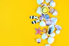 Fond d'été Accessoires étendus plats de plage de voyageur sur le fond jaune avec les coquillages, le chapeau miniature et les moc photos libres de droits