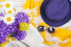 Fond d'été avec des accessoires de fleurs, de livre et de femme Photographie stock