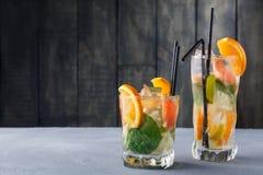Fond d'été avec des boissons et des fruits d'agrume au-dessus de bois rustique Photo stock