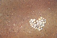 Fond d'été Coeur fait de coquilles sur la plage sablonneuse Photos stock