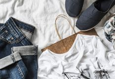Fond d'achats de l'habillement des femmes Jeans, espadrilles, T-shirt, écharpe et un sac de papier sur un fond clair, vue supérie Photographie stock
