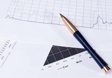 Fond d'affaires avec le stylo et les diagrammes financiers photographie stock libre de droits