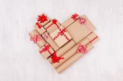 Fond d'amour - coeur des cadeaux avec les rubans rouges et des arcs sur le contexte en bois blanc, vue supérieure photos stock