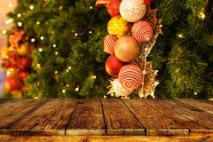 Fond d'arbre de Noël avec la décoration et bokeh léger brouillé avec la table en bois foncée vide de plate-forme Photographie stock libre de droits