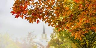 Fond d'automne avec le feuillage brillamment coloré dans le premier plan sur des arbres de côté et de blurre et église avec le cl photos stock