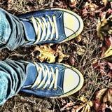 Fond d'automne Jambes d'une jeune femme dans espadrilles bleues Images stock