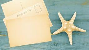 Fond d'heure d'été dans le rétro ton avec des cartes postales d'étoile et de vintage de mer sur le bois, l'espace de copie Photographie stock