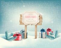 Fond d'hiver de Noël avec les présents et le bois Photographie stock