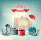 Fond d'hiver de Noël avec les présents et le conseil en bois Photographie stock libre de droits