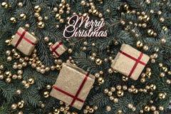 Fond d'hiver des branches de sapin Orné avec des babioles et des cadeaux d'or Vue supérieure Carte de Noël Inscription de Joyeux  images stock