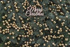 Fond d'hiver des branches de sapin Orné avec les babioles d'or et l'inscription de Joyeux Noël Carte de Noël images stock