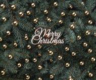 Fond d'hiver des branches de sapin Orné avec les babioles d'or et l'inscription de Joyeux Noël Carte de Noël photos libres de droits