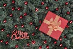 Fond d'hiver des branches de sapin Orné avec les babioles et le cadeau rouges Vue supérieure Carte de Noël Inscription de Joyeux  image stock