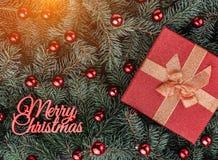 Fond d'hiver des branches de sapin Orné avec les babioles et le cadeau rouges Vue supérieure Carte de Noël Inscription de Joyeux  image libre de droits