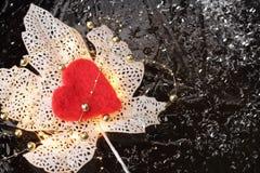 Fond d'hiver ou de Noël ou concept de valentine avec une feuille rougeoyante décorative blanche et un coeur rouge Photographie stock