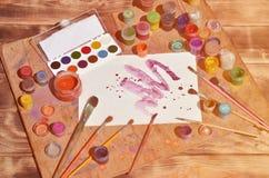 Fond d'image montrant l'intérêt pour la peinture et l'art d'aquarelle Une feuille de papier peinte, entourée par des brosses, pot images stock