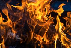 Fond d'incendie le rondin orange de flamme a roussi le plan rapproché sur un fond foncé photos stock