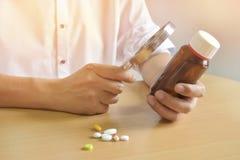 Fond dans la lumière chaude, docteur asiatique d'homme tenant une bouteille de pilules sur une table brune Utilisez une loupe pou images libres de droits