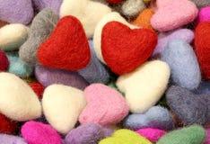 Fond de beaucoup de petits coeurs colorés de feutre et de hea de deux rouges Photo stock