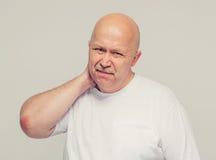 Fond de blanc de douleur cervicale de portrait d'homme supérieur Photo stock