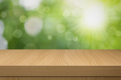 Fond de bokeh de feuillage avec la table en bois vide. Images libres de droits