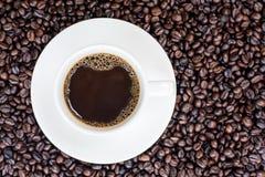Fond de café avec les haricots et la tasse blanche Copiez l'espace Photographie stock libre de droits